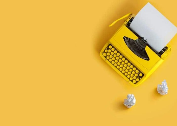 machine à écrire sur fond jaune avec des morceaux de papier