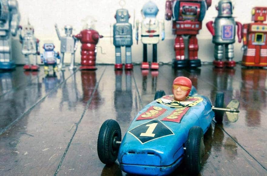 Une voiture miniature devant des robots jouets vintage