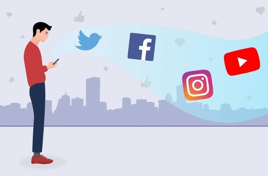 Homme debout avec son smartphone en train de vérifier ses réseaux sociaux