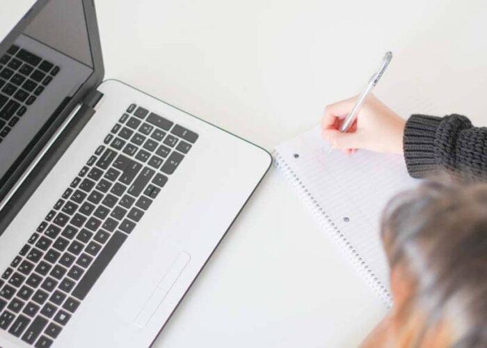 Une femme prend des notes devant son ordinateur
