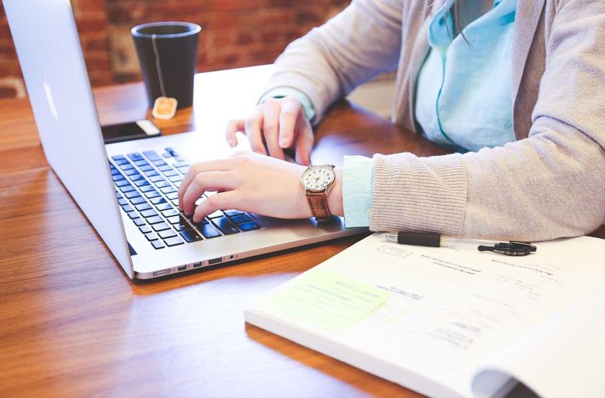 Une femme en train d'écrire sur le web avec un PC portable
