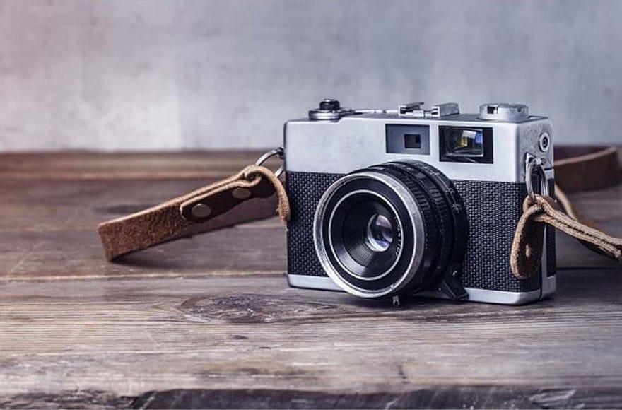 Un appareil photo vintage gris sur une table en bois