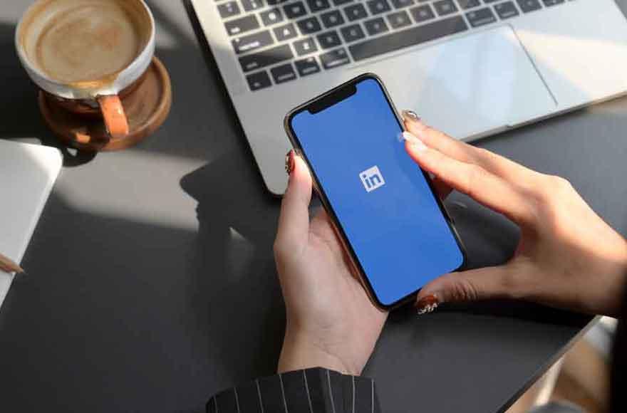 Une femme ouvre l'application Linkedin sur son smartphone